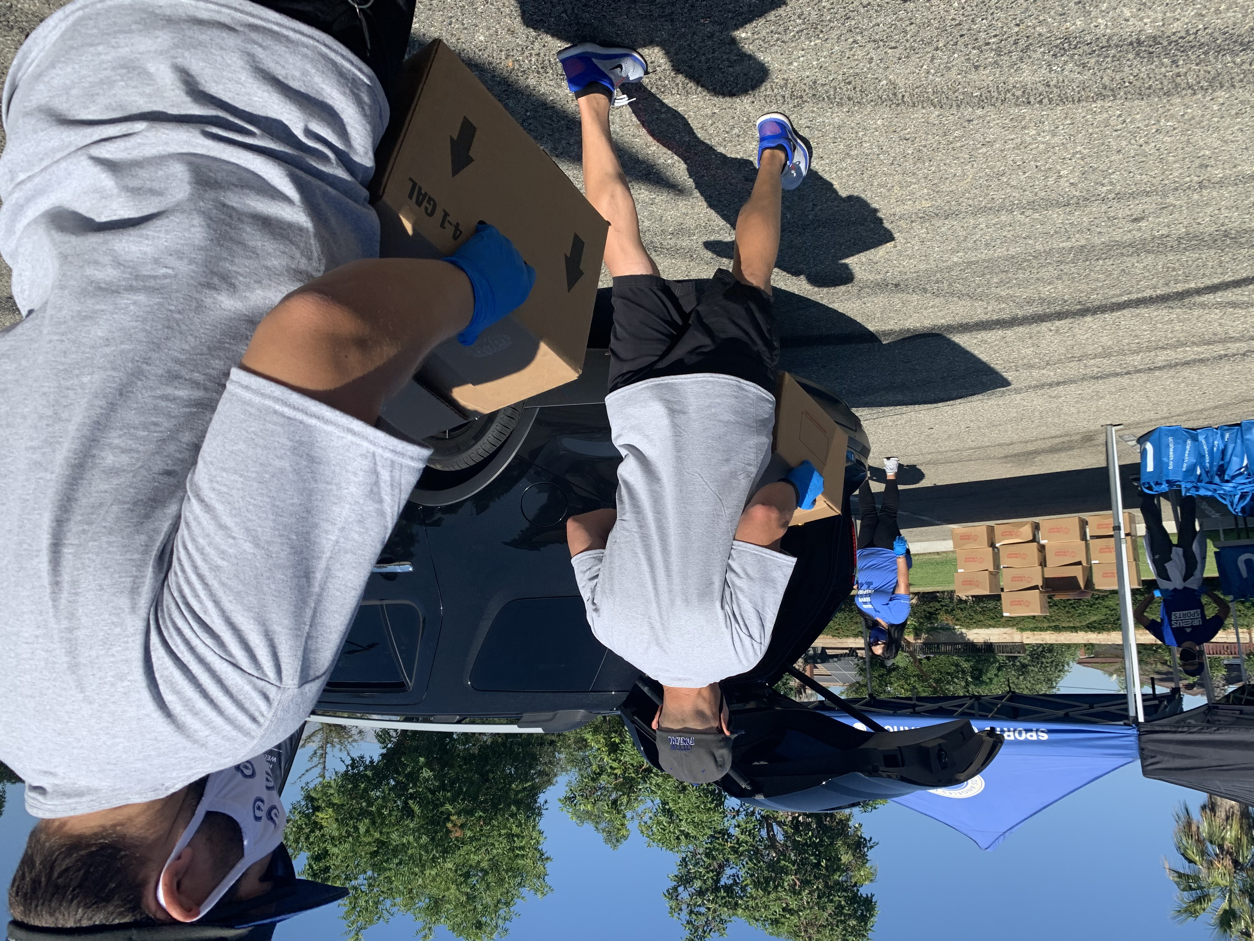 Male volunteers carry boxes to cars