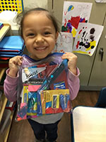 Girl from CDC holding bag of donated CVS school supplies