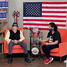 Centenarian Cliff and his friend Edna sit on orange chairs with an American flag on the wall behind them during his interview.