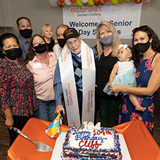 Cliff stands in front of his birthday cake with family and ESSC associates