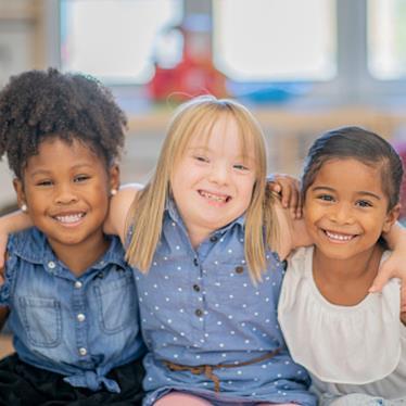 three children smiling at the camera