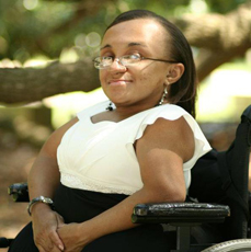 Black woman sitting in her wheelchair, smiling at the camera, wearing a black and white dress outside