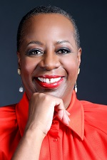 Angela F. Williams wearing a red top against a black background